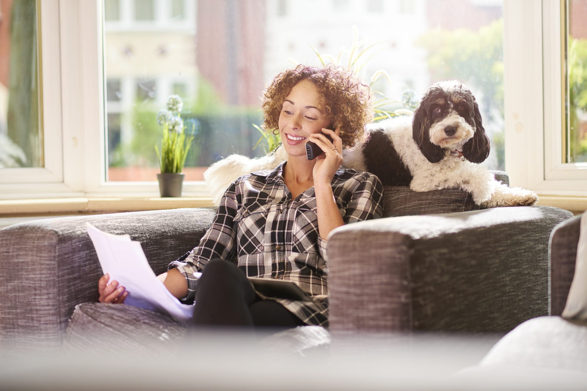Woman sitting on the couch on the phone holding paperwork out with her dog sitting behind her