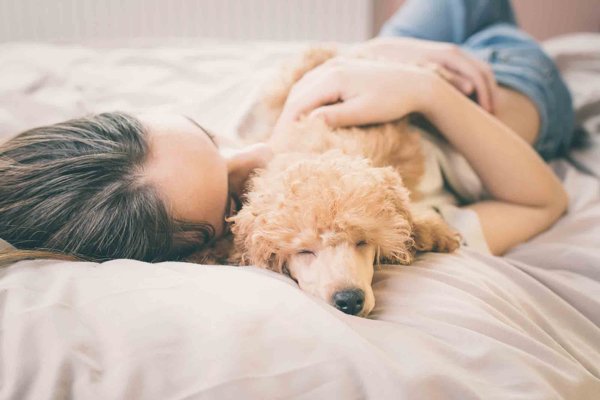 Young woman laying on bed snuggling with her dog